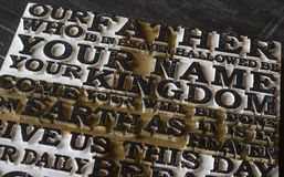 Word of the Lord`s Prayer on the old  black weathered wooden pla. Nk background. Close-up Royalty Free Stock Photo