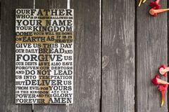 Word of the Lord`s Prayer on the shabby wooden plank with red Royalty Free Stock Photos