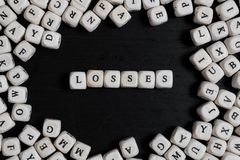 Word LOSSES on wooden cubes on a black wooden table. With copy space royalty free stock images