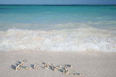Word Love on Beach Sand on Sand Beach and Ocean Royalty Free Stock Photos