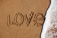 Word love on the beach is washed off with water Royalty Free Stock Photos