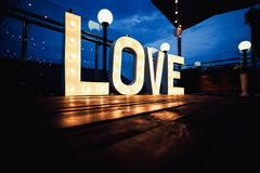 Word love from big, letters with glowing light bulbs on a dark b. Love word with glowing light bulbs standing on a floor Stock Photography