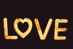Word love from big letters with glowing light bulbs on a dark Royalty Free Stock Photos