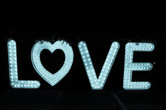 Word love from big letters with glowing light bulbs on a dark Stock Photo