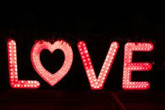 Word love from big letters with glowing light bulbs on a dark Stock Photos