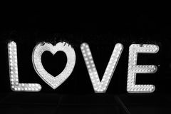 Word love from big letters with glowing light bulbs on a dark. Background Stock Photos