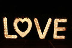 Word love from big letters with glowing light bulbs on a dark. Background Stock Photography