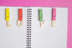 Word LOVE in blank book on pink background with space for text, Love icon, valentine`s day royalty free stock images