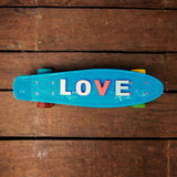 Word love on the blue penny board Stock Photos