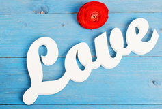 Word love. The word love on a blue wooden background, near red ranunculus Royalty Free Stock Photos
