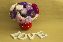 The word love and a bouquet of flowers. On a background of brown kraft paper Royalty Free Stock Images