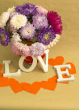 The word love and a bouquet of flowers. The word Loveorange heart and a bouquet of flowers on a background of kraft paper. Vertical Stock Images