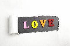 The word love. Broken sheet of paper behind the word love Royalty Free Stock Image