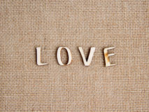 Word love on burlap. Wooden Word love on burlap Royalty Free Stock Photos