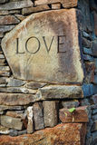 The Word Love Carved on a Stone. Within a wall of natural stone Stock Image