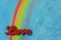 The word love with a colorful rainbow and blue sky background Stock Image