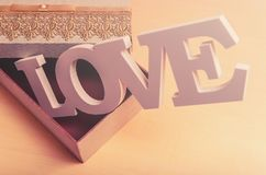 Word LOVE coming out of a craft box with the cover semi open. Concept of love for valentine`s day, mother`s day, father`s day and general love Royalty Free Stock Photography