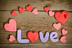 Word Love composition on the wooden board with hearts Royalty Free Stock Photo