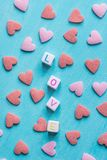 Word Love Constructed from Stacked Letter Cubes. Pink Red Sugar Candy Sprinkles Scattered on Light Blue Background. Valentine Royalty Free Stock Photography