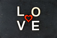 Word LOVE created of wood letters, red wooden heart shape in the middle Royalty Free Stock Photos