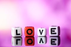 Word love from cubes with reflection on bright blurred background. Word love from cubes with reflection on blurred background royalty free stock photo