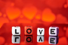 Word love from cubes with reflection on bright blurred background. Word love from cubes on bright blurred background stock photos