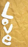 The word Love in cut out magazine letters put on brown paper. Royalty Free Stock Images