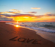 Word love on sand sunset beach Royalty Free Stock Images