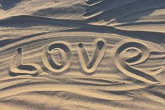 Word love drawn on sand in sunset sunlight as love background. Stock Photo