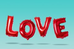 Word love in english alphabet from red balloons on a bright background. Minimal love concept