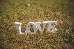 The word love in English of white wooden letters on the green grass in the Park outdoors, copy space. Decoration for wedding, stock photos