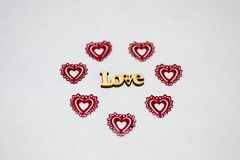 Word Love in an environment of red hearts. Wooden inscription. Hearts openwork plastic royalty free stock photos