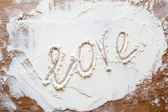 The word love on the flour. Amorous chef made the word love with his finger on the flour, crumbled on a cutting board royalty free stock photography