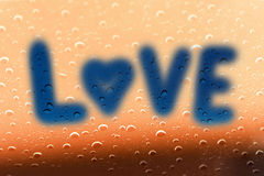 The word Love on glass with raindrop.  Stock Images