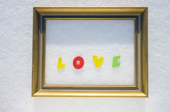 Word love in golden picture frame on snow. valentine day Royalty Free Stock Images