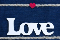 The word Love with heart and rope border on denim. Wooden Love text with small red wood heart with rope braid border on blue denim backdrop royalty free stock photo
