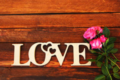 The word love and a heart with roses Royalty Free Stock Images