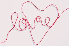 Word love and heart shape written with red yarn thread on white. Word love and heart shape written with red yarn thread over white background. Horizontal view stock photography