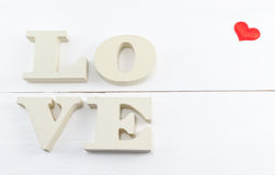 Word love with heart shaped on white wooden background. Stock Images