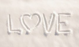 Word love  with a heart, written in fresh powdery snow Royalty Free Stock Photos