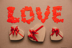 Word Love from hearts and gift boxes in the shape of hearts. Gifts for Valentine's Day. Royalty Free Stock Image