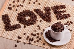 Word love laid out from coffee. White cup with coffee Stock Photos