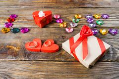 Word love laid out young hearts, two boxes for a gift in the shape of hearts and decorative hearts on wooden background. stock images
