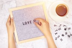 Word LOVE on letter board with woman`s hand holding heart symbol on white marble desk background with coffee cup. Word LOVE on letter board with woman`s hand royalty free stock photo