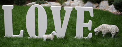 Word LOVE in letter figures. Photo closeup of word love written in white separate letter figures font sheep and lamb figurines standing on green grass outdoor on Stock Photography