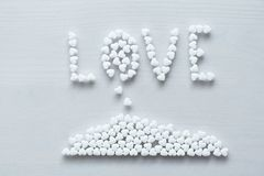 The word love is lined or written from white hearts on a white background. Design with copy space. Top view stock image