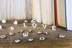 The word love a lot of hearts on a background of books on a wooden table. Stock Photos