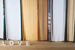 The word love a lot of hearts on a background of books on a wooden table Royalty Free Stock Photo