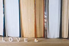 The word love a lot of hearts on a background of books on a wooden table. Royalty Free Stock Photography