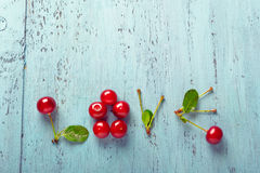 Word Love made with cherries on old board Royalty Free Stock Images